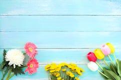 在蓝色木背景的五颜六色的花花束 免版税库存照片