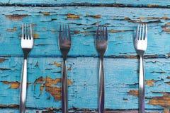 在蓝色木背景的四把叉子 库存图片