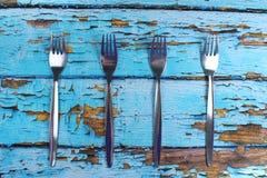 在蓝色木背景的四把叉子 免版税图库摄影