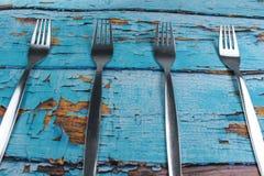 在蓝色木背景的四把叉子 库存照片