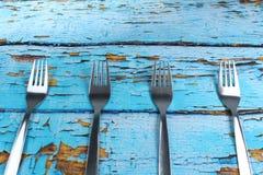在蓝色木背景的四把叉子 免版税库存照片
