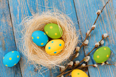 在蓝色木背景的复活节彩蛋 库存图片