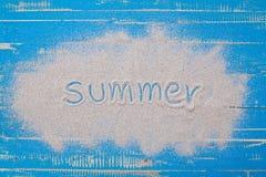 在蓝色木背景的夏天标志白色沙子 免版税库存图片