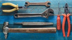 在蓝色木背景的工具:螺丝刀,钳子,小块,锤子,少年,文件,可调扳手 顶视图 免版税库存图片