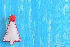 在蓝色木背景的手工制造毛毡圣诞树与文本的拷贝空间 抽象空白背景圣诞节黑暗的装饰设计模式红色的星形 袋子看板卡圣诞节霜klaus ・圣诞老人天空 免版税图库摄影