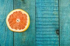 在蓝色木背景的新鲜的切的葡萄柚 免版税库存照片