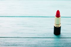在蓝色木背景的桃红色唇膏 复制空间 组成产品和化妆用品概念 选择聚焦 免版税库存图片