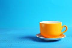 在蓝色木背景的橙色杯子 库存照片