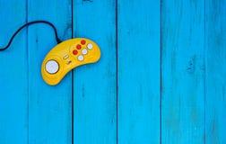 在蓝色木背景的比赛控制器 黄色控制杆 库存照片