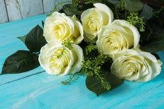 在蓝色木背景的白玫瑰 免版税库存图片