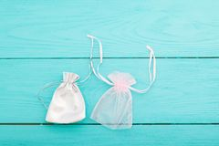 在蓝色木背景的白色银色松紧带袋子 织品棉花小袋子 首饰囊 顶视图 复制空间并且嘲笑  库存图片