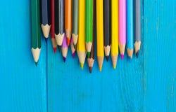 在蓝色木背景的色的铅笔 免版税库存图片