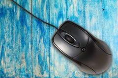 在蓝色木背景的计算机老鼠 库存照片