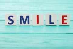 在蓝色木背景的词微笑 选择聚焦 复制空间 概念查出的刺激白色 免版税库存图片