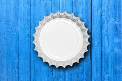 在蓝色木背景隔绝的玻璃啤酒瓶盖帽,顶视图 3d例证 免版税库存照片