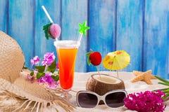 在蓝色木头和沙子性的热带鸡尾酒在海滩 库存照片