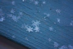 在蓝色木头的雪花 库存照片