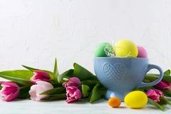 在蓝色杯子和桃红色郁金香背景的复活节手画鸡蛋 免版税库存照片