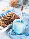 在蓝色杯子的倾吐的牛奶与蛋糕的早餐 垂直 免版税图库摄影