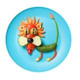 在蓝色板材做的滑稽的菜狮子 库存图片