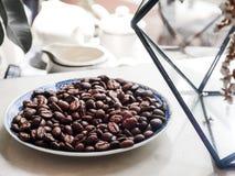 在蓝色板材的咖啡豆在与咖啡壶的桌上 免版税库存照片