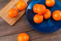 在蓝色板材的桔子在黑暗的木桌上 图库摄影