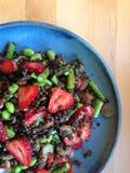 在蓝色板材的草莓、芦笋、edamame和扁豆沙拉 免版税库存照片