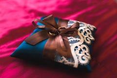 在蓝色枕头的婚戒 库存图片