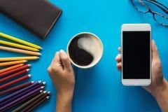 在蓝色桌上的一个手举行智能手机黑色屏幕 免版税库存图片