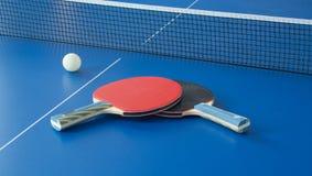 在蓝色桌上的乒乓球黑和红色球拍 免版税库存照片