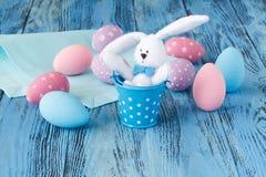 在蓝色桌上的欢乐复活节彩蛋与玩具兔宝宝 免版税图库摄影
