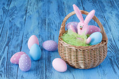 在蓝色桌上的欢乐复活节彩蛋与玩具兔宝宝 库存照片