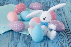 在蓝色桌上的欢乐复活节彩蛋与玩具兔宝宝 图库摄影