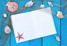 在蓝色桌上的笔记本与海扇壳和红色海星 库存照片