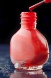 在蓝色桌上的红色指甲油与反射 免版税图库摄影