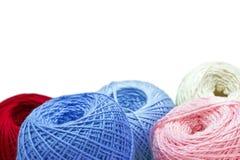 在蓝色桌上的编物纱反对被弄脏的背景 关闭多色的羊毛球 免版税库存照片