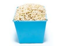 在蓝色桶的未煮过的糙米 免版税库存照片