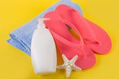 在蓝色毛巾和晒黑奶油色化妆水和海星的桃红色凉鞋触发器在黄色背景 免版税库存照片