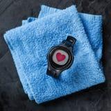 在蓝色毛巾的心率显示器在足球附近 免版税图库摄影
