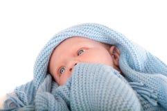 在蓝色毯子的逗人喜爱的男婴的纵向 图库摄影