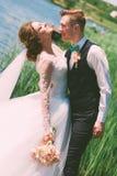 在蓝色池塘附近的新郎拥抱的微笑的新娘 免版税图库摄影