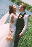 在蓝色池塘附近的新郎拥抱的新娘 免版税库存照片