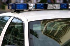 在蓝色汽车上面点燃警察 库存图片