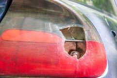 在蓝色汽车的捣毁的和损坏的后方中止光,损坏由艺术品破坏者或在崩溃事故关闭  图库摄影