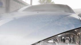 在蓝色汽车的敞篷的下泡沫奔跑 在街道上的洗车 股票录像