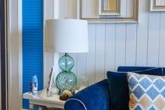 在蓝色沙发旁边的玻璃桌照明设备 免版税库存图片