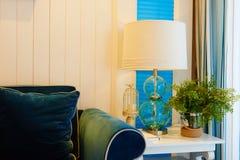 在蓝色沙发旁边的玻璃桌照明设备 库存照片