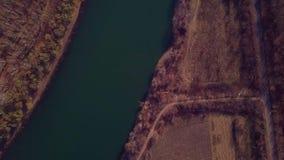 在蓝色河和农田的缓慢的寄生虫飞行 股票录像