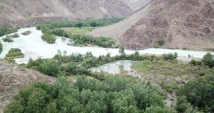 在蓝色河的飞行 宽河 在绿草、小山、山和干草原岸  股票视频