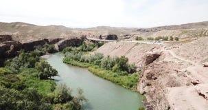 在蓝色河的飞行 宽河 在绿草、小山、山和干草原岸  股票录像